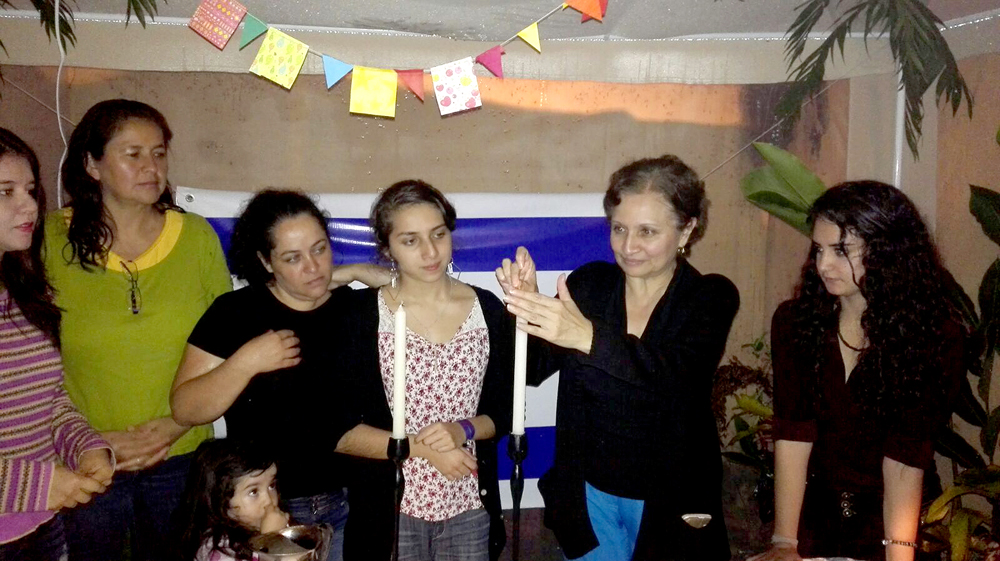 Rivka Orantes (third from right) and her mother, Jeannette Orantes (second from right), lighting candles for Sukkot with members of Asociacion Judia Reformista de Guatemala Adat Israel Photo by ALVARO ORANTES