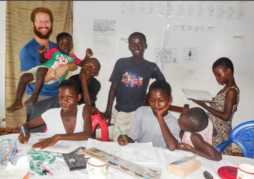 Loren Berman, Kulanu Teaching Fellow, with the elementary and middle school children in Sefwi Wiawso, Ghana, taking a break while practicing the Aleph-Bet