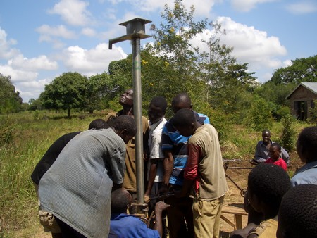 Villagers get water from the repaired borehole (Photo by Yoash Mayende)
