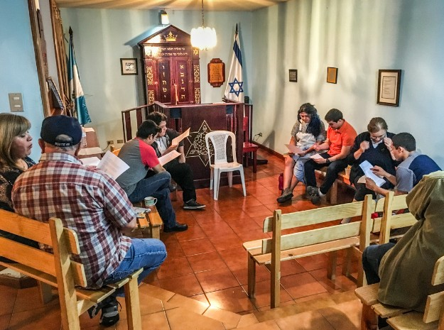 Community members of all ages gather in the synagogue to read  Spanish Nevi'im texts in chevruta study as part of a weekly evening  class on the Hebrew prophets.