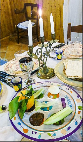 "Traditional Italian Seder Plate with Sephardi candelabra to kindle light for Yom Tov. In Italy, three candles are used. The middle candle serves as the ""shamus"" to light the other two. (Photo by Rabbi Barbara Aiello)"